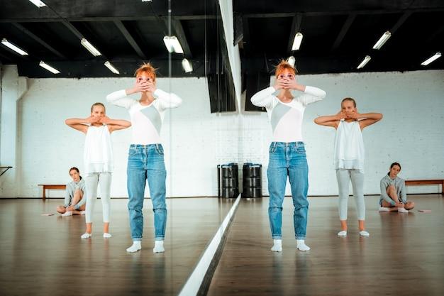 Dansoefening. roodharige balletdocent en haar studenten voelen zich geconcentreerd tijdens het oefenen van elementen van moderne dans