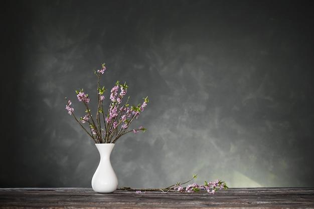 Daphne bloemen in vaas op oude houten tafel op donkere oppervlaktemuur