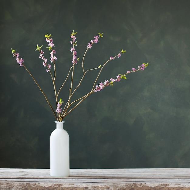 Daphne bloemen in vaas op oude houten tafel op groene achtergrondmuur