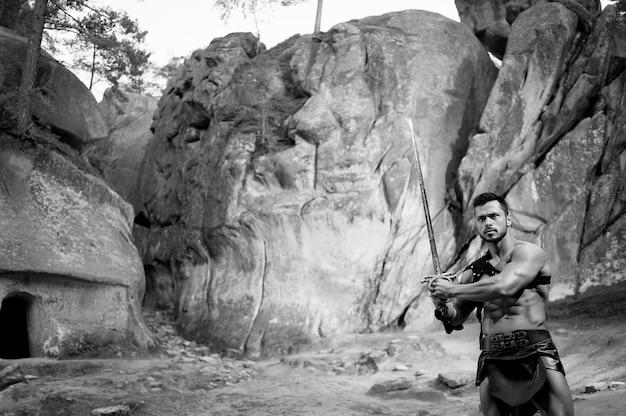 Dapper hart. zwart-wit portret van een jonge krijger met een prachtig atletisch krachtig lichaam klaar om te vechten met een zwaard dat bij de rotsen poseert