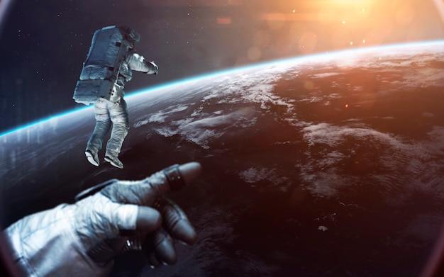 Dappere astronauten die naar de prachtige blauwe aarde kijken. mensen in de ruimte. elementen van deze afbeelding geleverd door nasa