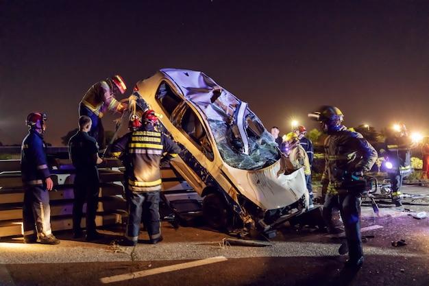 Dappere brandweerlieden die de man uit de gecrashte auto proberen te bevrijden.