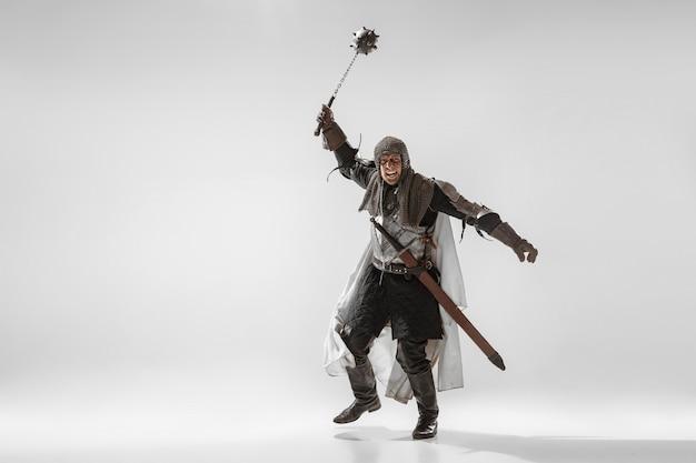 Dappere gepantserde ridder met professionele wapengevechten geïsoleerd op witte studioachtergrond.