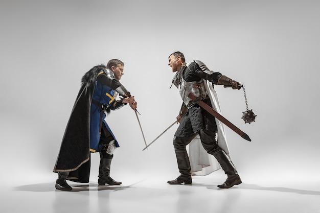 Dappere gepantserde ridders met professionele wapengevechten geïsoleerd op witte studioachtergrond.