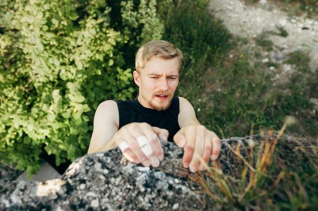 Dappere jonge man klimt de top van de klif