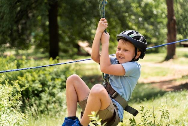 Dappere jongen die plezier heeft in een avonturenpark