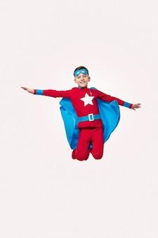 Dappere jongen in superheld kostuum springen