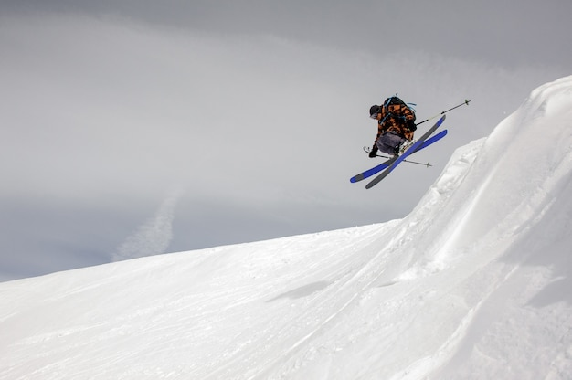Dappere skiër stijgt van de grond terwijl hij van de besneeuwde bergen glijdt