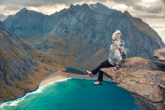 Dappere vrouw over turquoise zeewater tussen de bergen op het strand van kvalvika uitzicht vanaf mount ryten