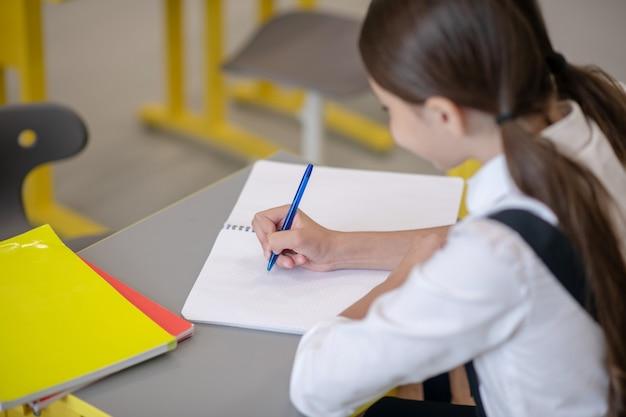 Darkhaired meisje in schooluniform is ijverig schrijven met pen in notitieblok achter schoolbank