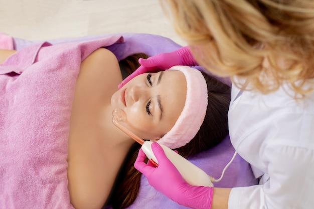 Darsonvalization van het gezicht of verjonging van het gezicht met behulp van elektrotherapie