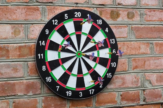 Dart in bullseye op het doelwit met vele andere darts