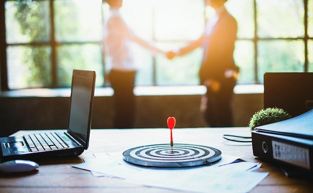 Dart-poort naar het midden van het doel op het bureau, zoals een succesbedrijf.