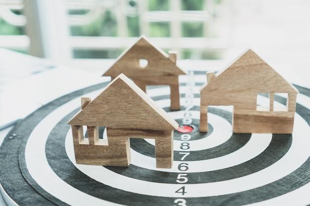 Dartbord dat op het nummercentrum slaat met miniatuur houten huismodellen. succes goud van eigendom