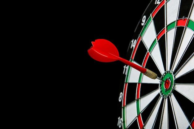 Dartbord en darts geïsoleerd op zwart