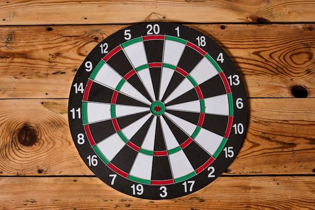 Dartbord hangt in het midden van een houten muur