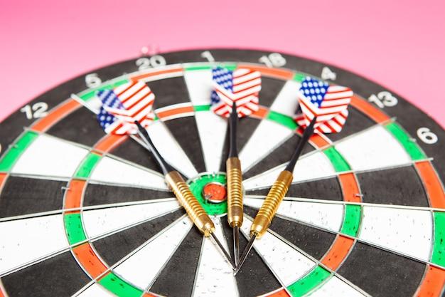 Darten en darts op een roze achtergrond. doel concept
