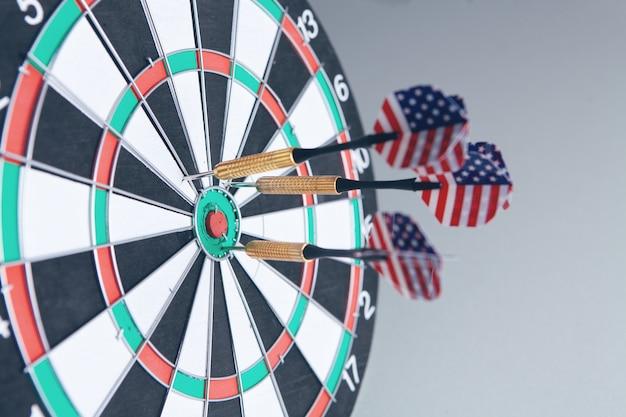Darten met amerikaanse vlag die in het doelcentrum van het dartbord raakt