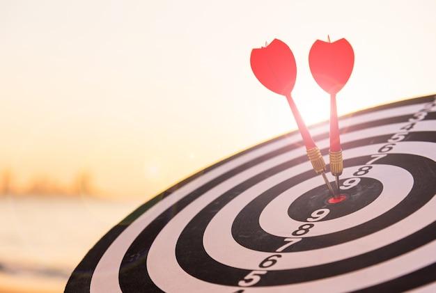 Dartpijl die in het midden van het bullseye-dartbord raakt, is het doelwit van uitdagende bedrijven