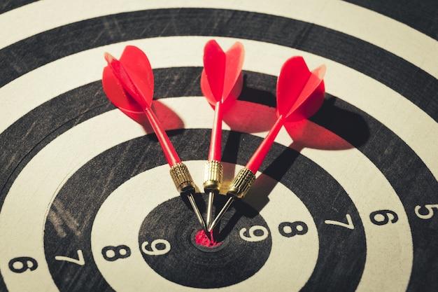 Dartpijl raakt in het doelcentrum van dartbord. concept van het succes