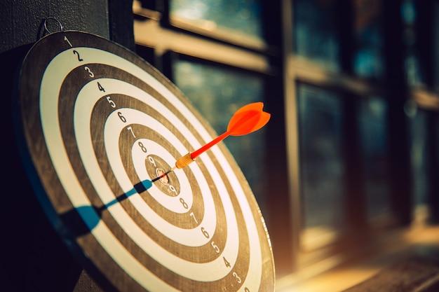 Dartpijl sloeg op bulleyes van dartbord om aan te geven dat het bedrijf het doel bereikte met een donkere toonbeeldstijl. doel en doel als concept.