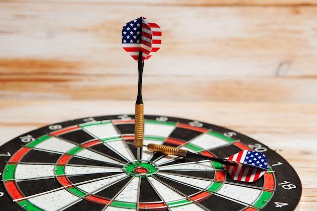 Darts in het midden van het doel op een houten achtergrond