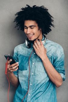 Dat is echt een geweldige afspeellijst. jonge afrikaanse man die een koptelefoon draagt en zijn smartphone gebruikt