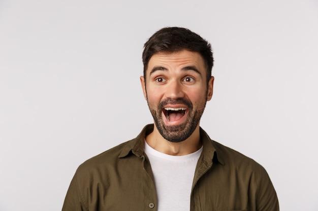 Dat is hilarisch. geamuseerd en verwonderd, opgewonden aantrekkelijke bebaarde volwassen man in jas, kijk naar links en lachend om grappige gebeurtenis, lachend verbaasd, bezoek interessante partij