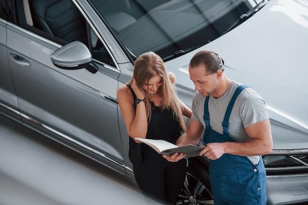 Dat is wat ik heb gebruikt. resultaten van reparatie. zelfverzekerde man die laat zien wat voor soort schade haar auto is opgelopen.