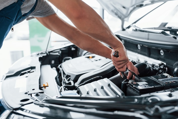 Dat moet worden opgeladen. proces van het repareren van auto na ongeval. man aan het werk met motor onder de motorkap