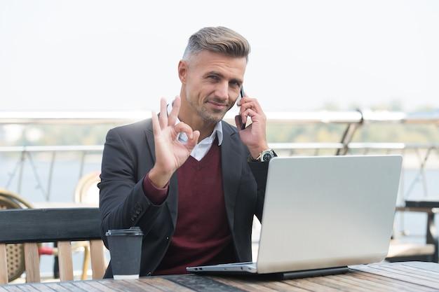 Dat noem ik nou ok. knappe man toont ok praten over de telefoon. overeenkomst en toestemming. projectmanager werk in cybercafé. moderne levensstijl. zakelijke communicatie. mobiele technologie.