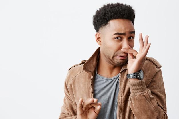 Dat ruikt heel erg. close-up portret van jonge grappige donkere man met afro kapsel sluitende neus met vingers, voelend advertentie van walgelijke geur van vuilnisbelt in stad.