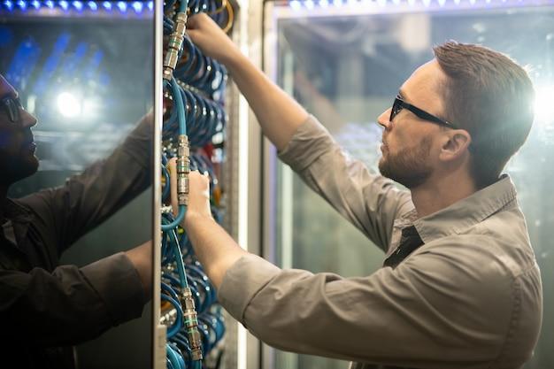Datacenteringenieur die kabels onderzoeken