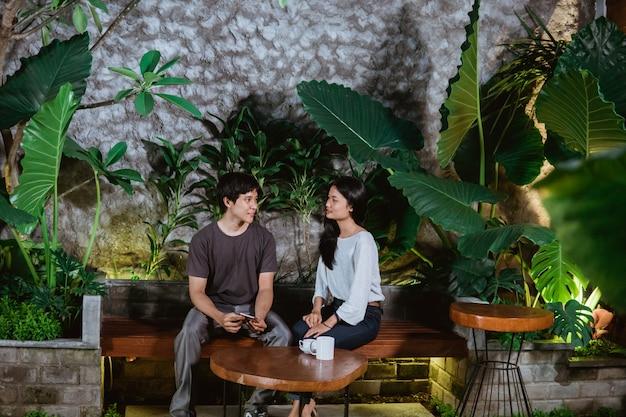 Dating een paar aziatische tieners zittend op houten banken in de tuin van het huis
