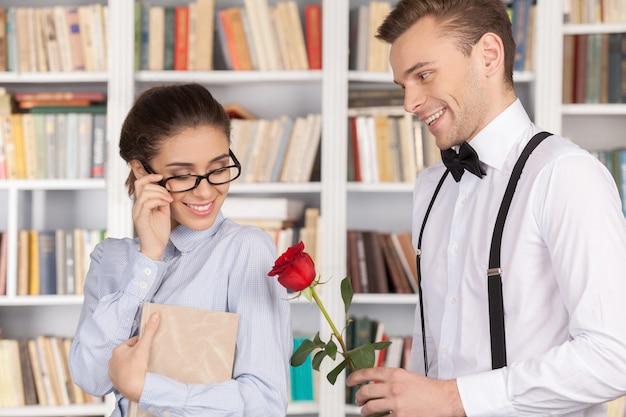 Datum in bibliotheek. vrolijke jonge nerdman die een rode roos geeft aan een mooie jonge vrouw met een bril terwijl hij in de bibliotheek staat