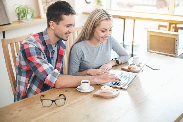 Datum in café. jong koppel in café met stijlvol interieur. studenten met heerlijke koffiedrankjes. ze chatten, gebruiken laptop en glimlachen