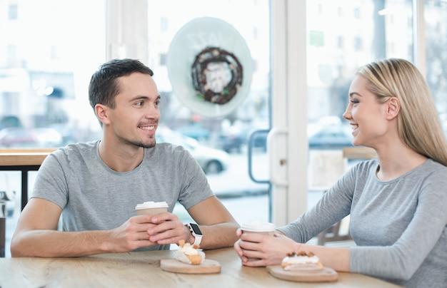 Datum in café. jong koppel in café met stijlvol interieur. studenten met heerlijke koffiedrankjes. ze kletsen en lachen