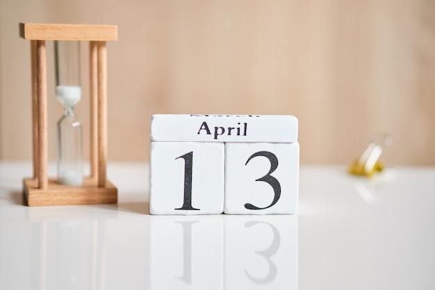 Datum op witte houten blokjes - de dertiende, 13 april op een witte tafel.
