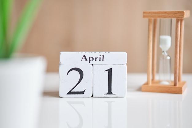 Datum op witte houten blokjes - de eenentwintigste, 21 april op een witte tafel.