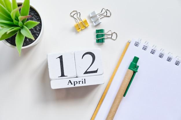 Datum op witte houten blokjes - de twaalfde, 12 april op een witte tafel. bovenaanzicht.