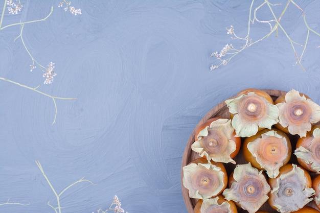 Datum pruimen in een houten schotel op blauwe achtergrond