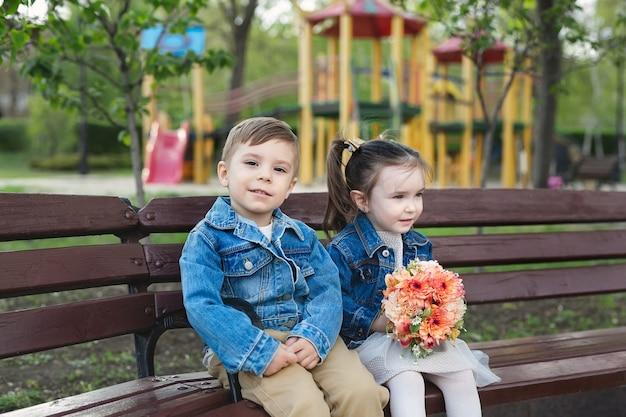 Datum van een kleine jongen en een meisje in het park op een bankje met een boeket bloemen.