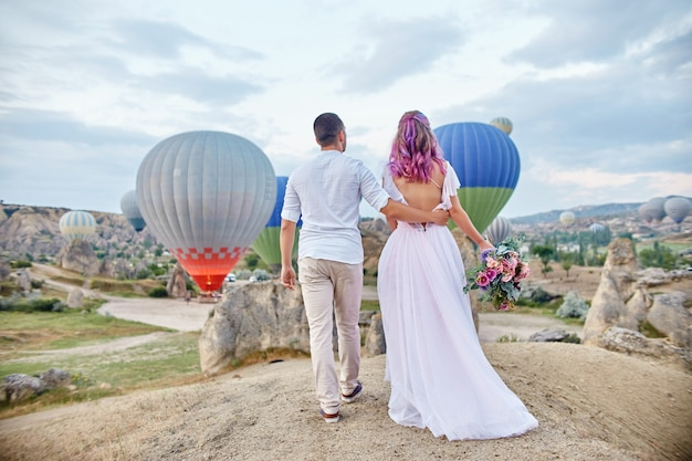 Datum van verliefde paar bij zonsondergang tegen ballonnen