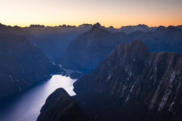 Dawn gloed over darran mountains en milford sound piopiotahi fiordland national park