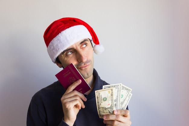 Daydreamer-man met kerstmuts glimlacht terwijl hij zijn paspoort en contant geld positief denkt