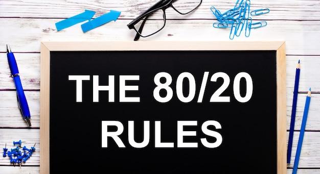 De 80 20 regel geschreven op een zwart notitiebord naast blauwe paperclips, potloden en een pen.