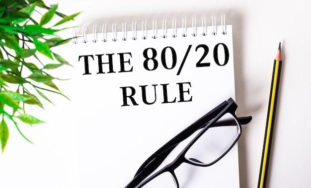 De 80 20 regel is geschreven in een wit notitieboekje naast een potlood, een bril met een zwart frame en een groene plant.