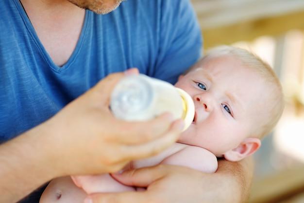 De aanbiddelijke consumptiemelk van de babyjongen van fles in vaderhanden
