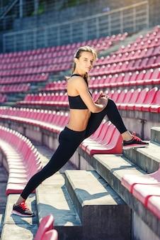 De aanbiddelijke sportieve vrouw maakt het uitrekken zich bij het stadion. sport, gezondheidszorg concept