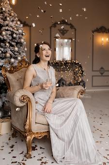 De aanbiddelijke vrouw in zilveren kleding zit vóór een kerstboom met een champagneglas in haar hand
